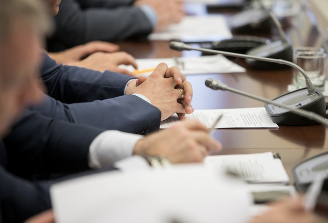 Man sitting by table with his hands over document