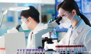 Researcher looks in lab microscope