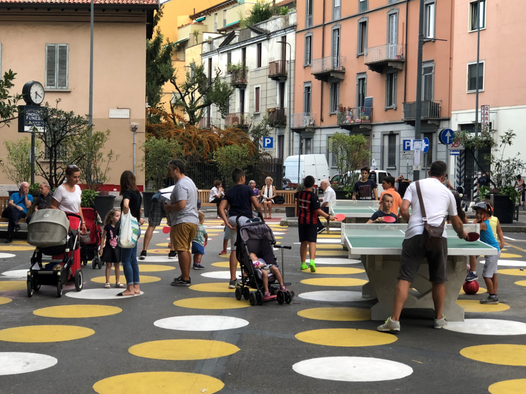 Ping-pong, picnic tables and planters create a neighborhood gathering place out of a parking lot in an outlying Milan neighborhood.