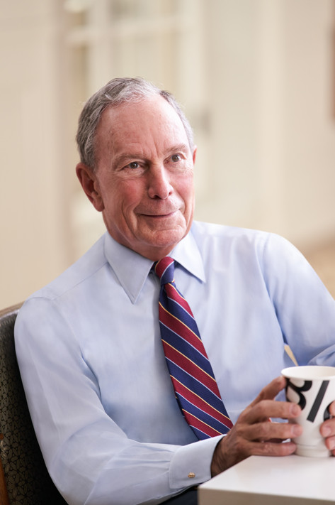 Photo of Mike Bloomberg at a desk.