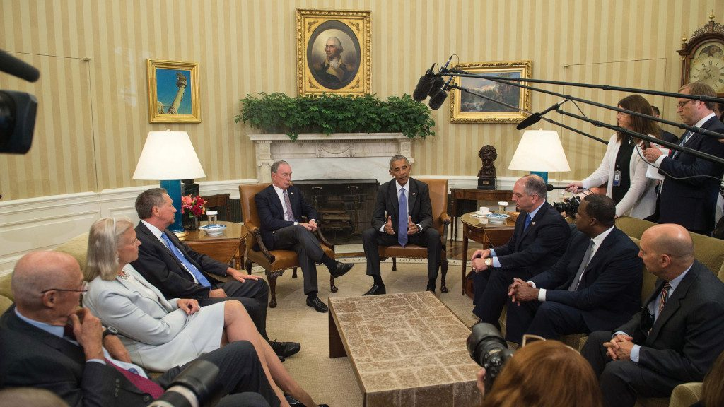 Photo of Mike discussing global trade deals with Obama and others.