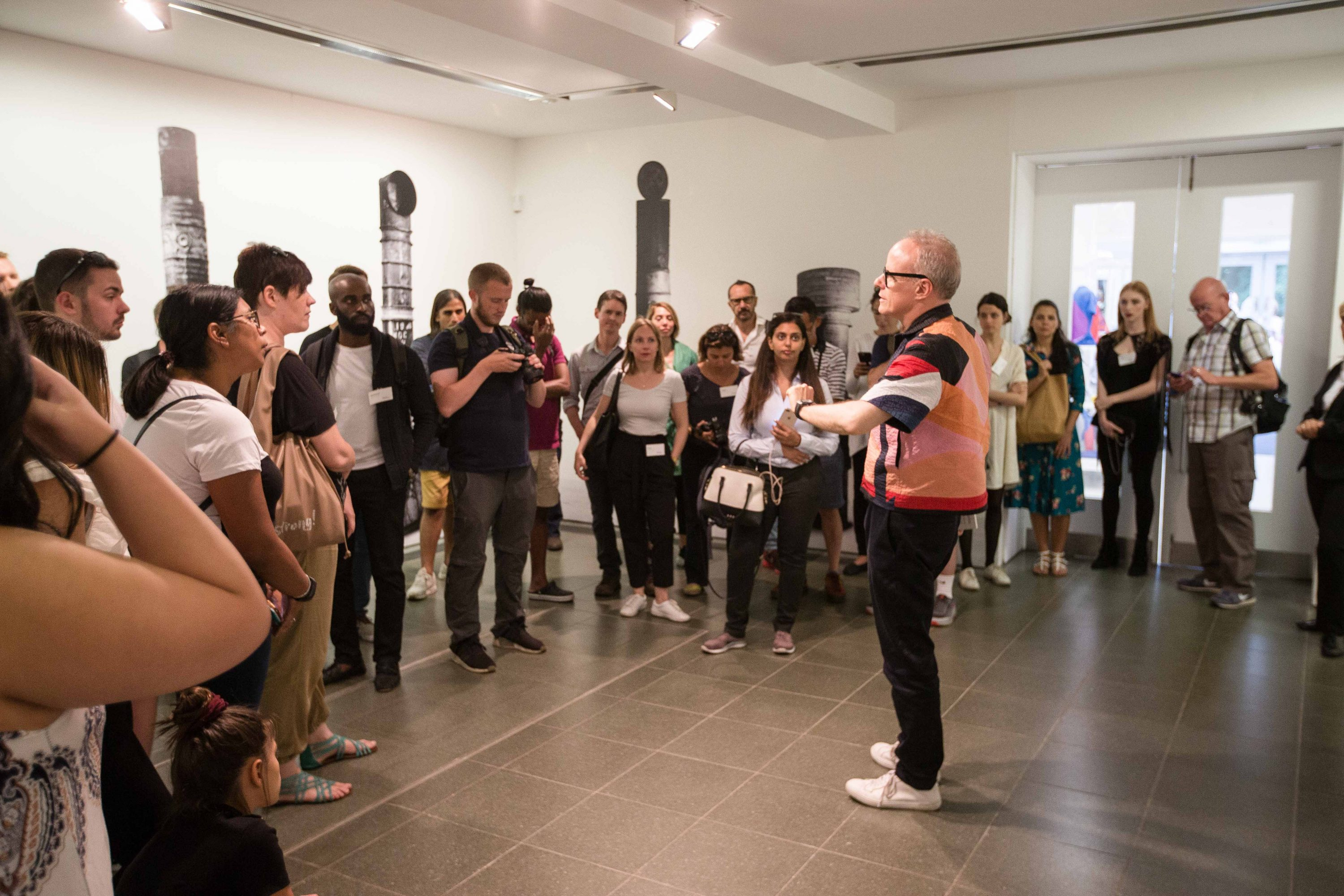 """Instagrammers gather to hear Hans Ulrich Obrist lead a tour of the """"Christo and Jeanne-Claude: Barrels and The Mastaba 1958–2018"""" exhibition at the Serpentine Galleries in London."""