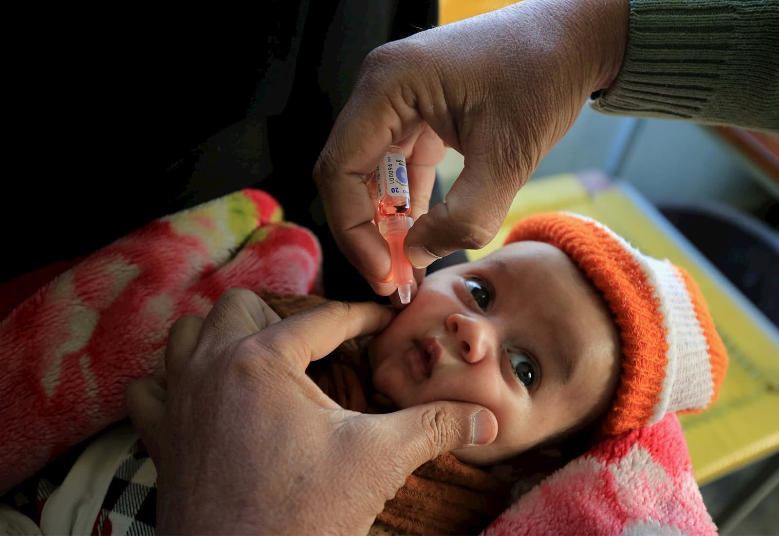 A health worker administers polio vaccine to children during a three-day countrywide vaccination campaign in Peshawar, Pakistan.
