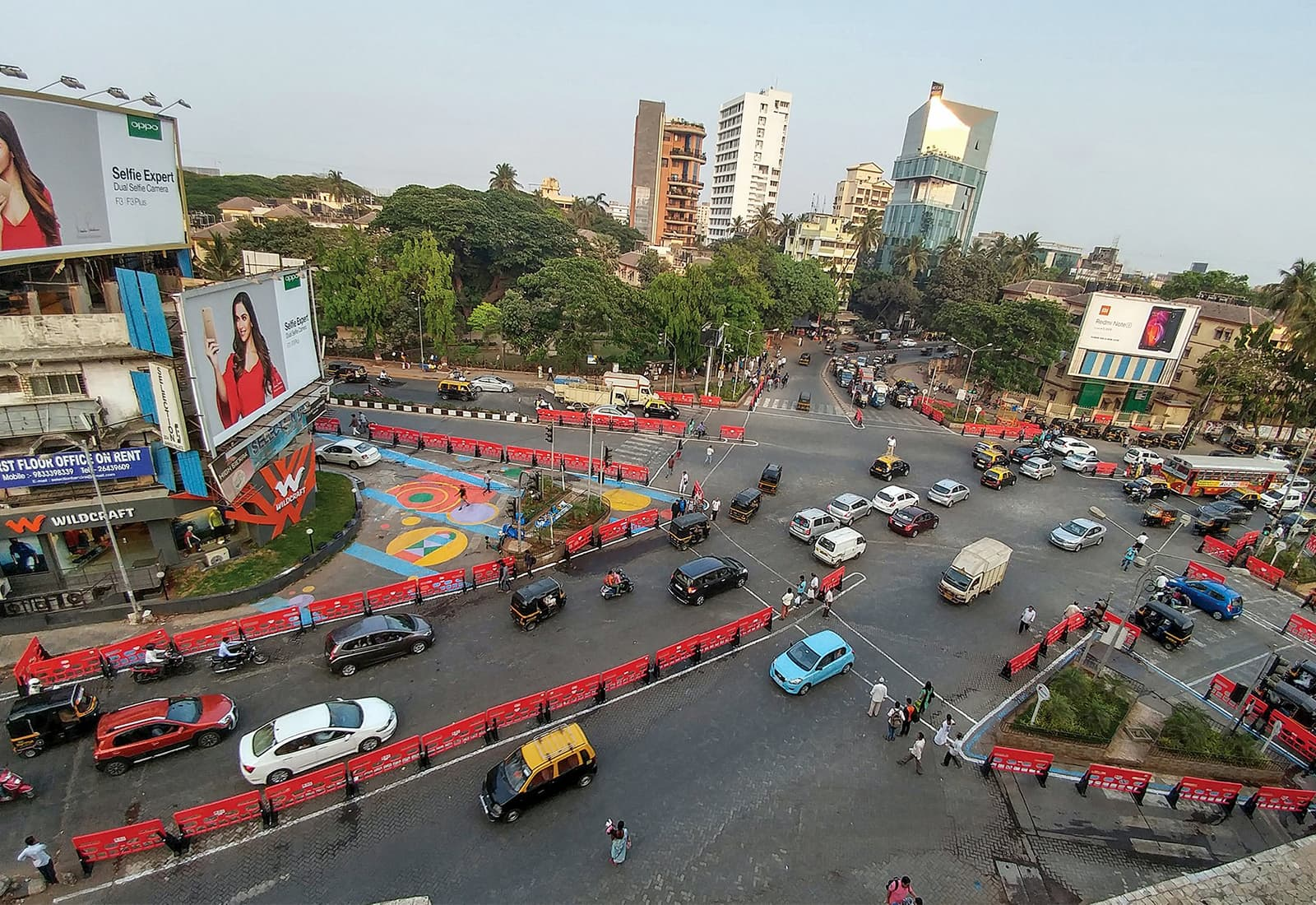 A busy intersection in Mumbai, India was redesigned with colorful barriers and crosswalks making pedestrians, cyclists, and drivers safer. Photo credit: WRI India