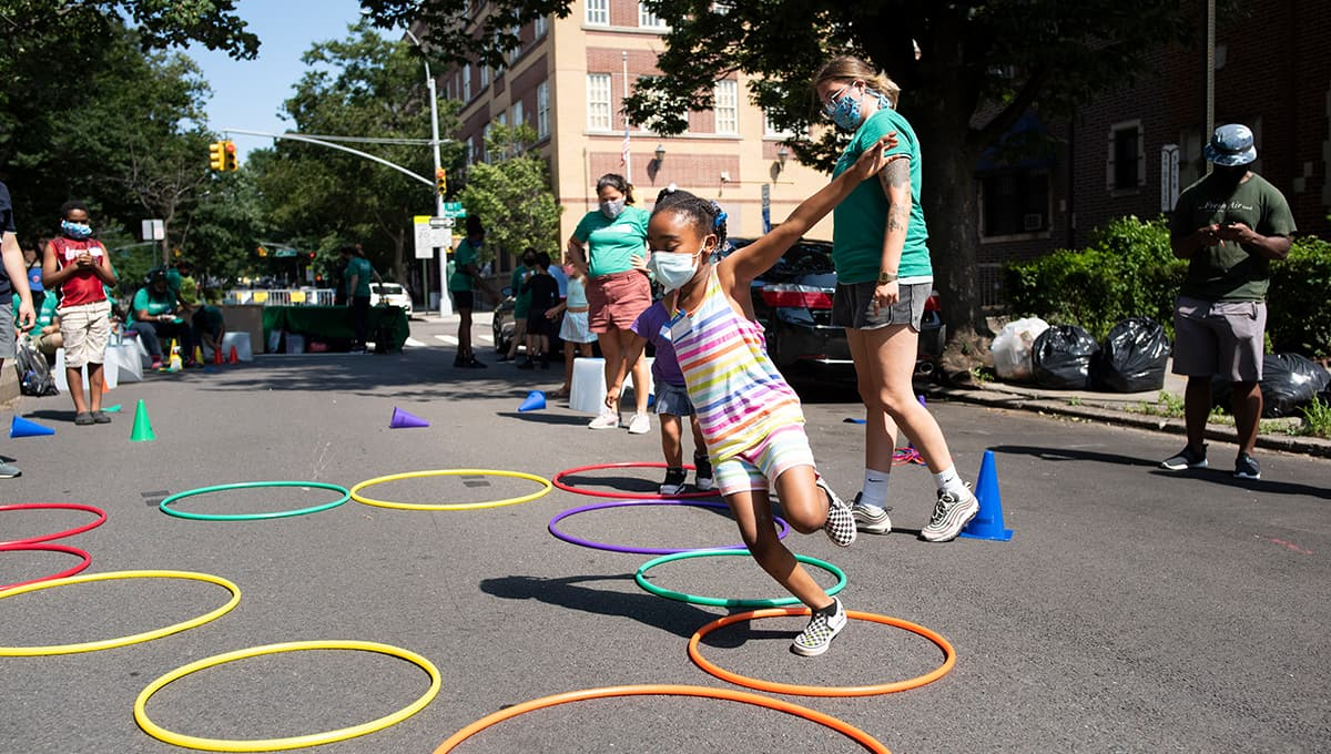 A young girl plays outside in the Jackson Heights neighborhood in Queens, New York during Fresh Air Fund Summer Space, an outdoor summer program for youth supported by Bloomberg Philanthropies, Ford Foundation, and the JPB Foundation.