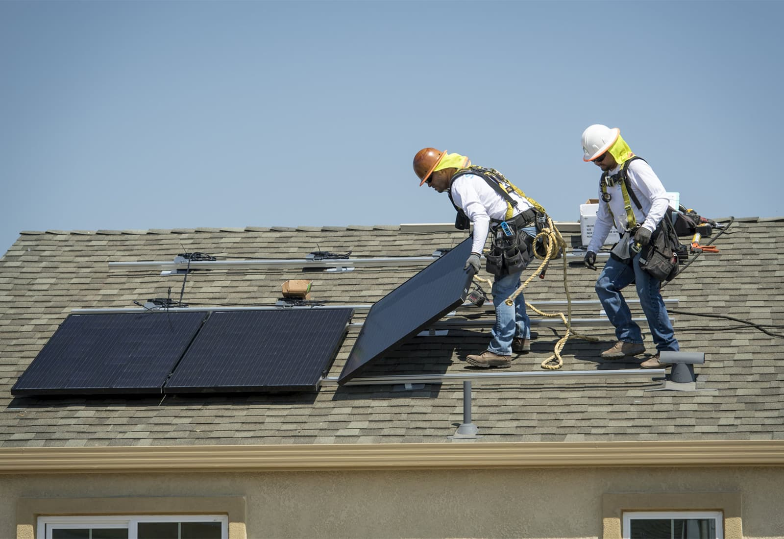 Contractors install SunRun Inc. solar panels on the roof of a new home at the Westline Homes Willowood Cottages community in Sacramento, California. Photo credit: David Paul Morris and Bloomberg