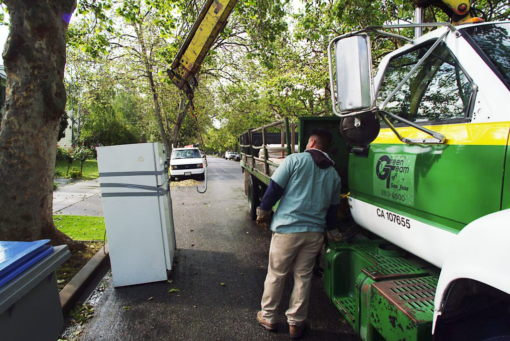 A city worker uses a truck to collect a refrigerator from a curb