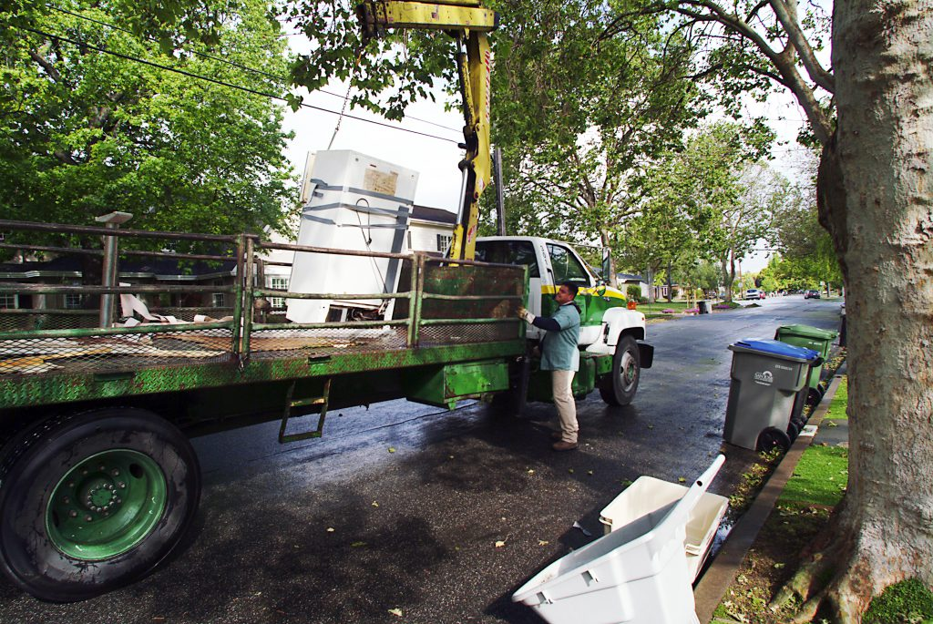 A city worker loads a refrigerator onto a large truck through San Jose's Large Item Collection program
