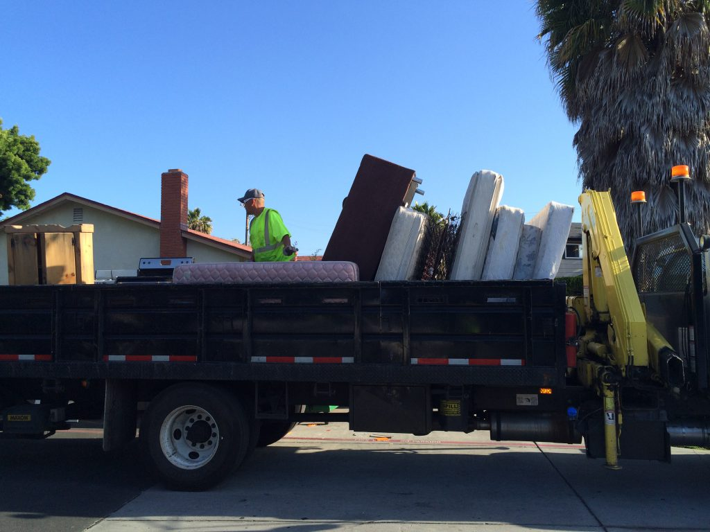 A city worker loads items onto a truck as part of San Jose's large item collection program