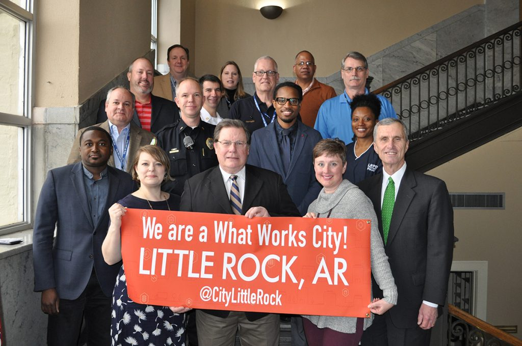"Little Rock Mayor and staff hold a banner that reads ""We are a What Works City!"""
