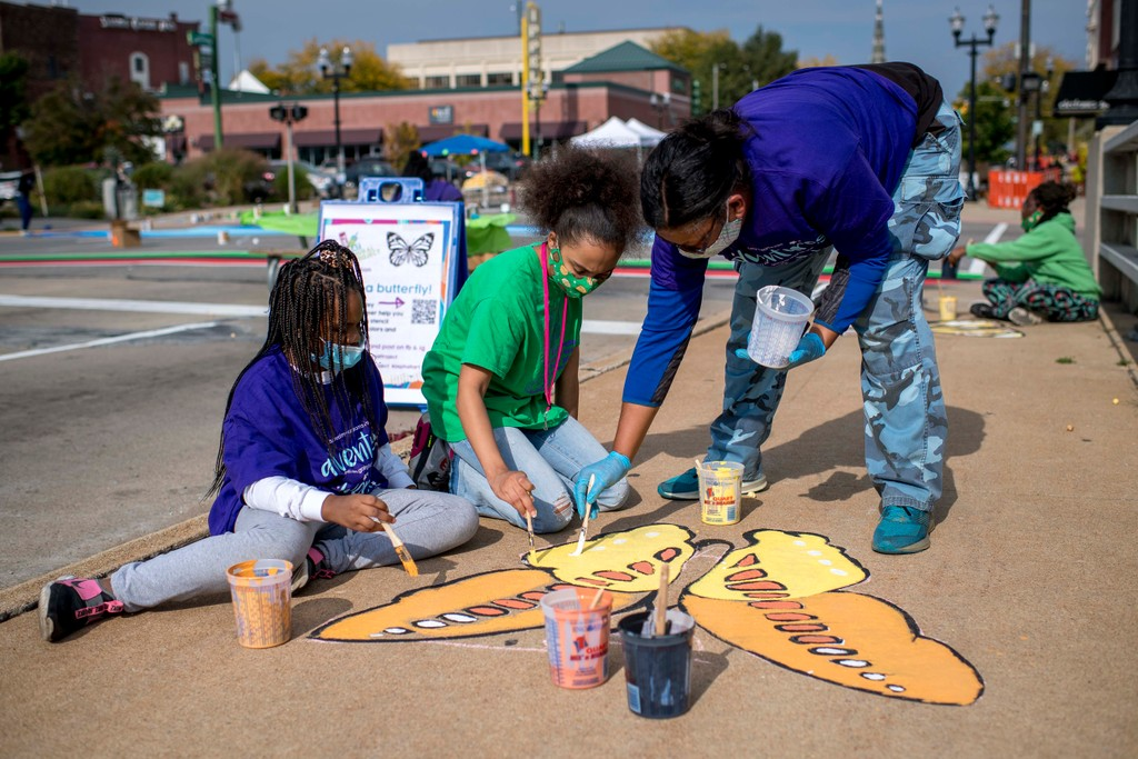 Painting butterflies along Court Street during the Great Mural Project