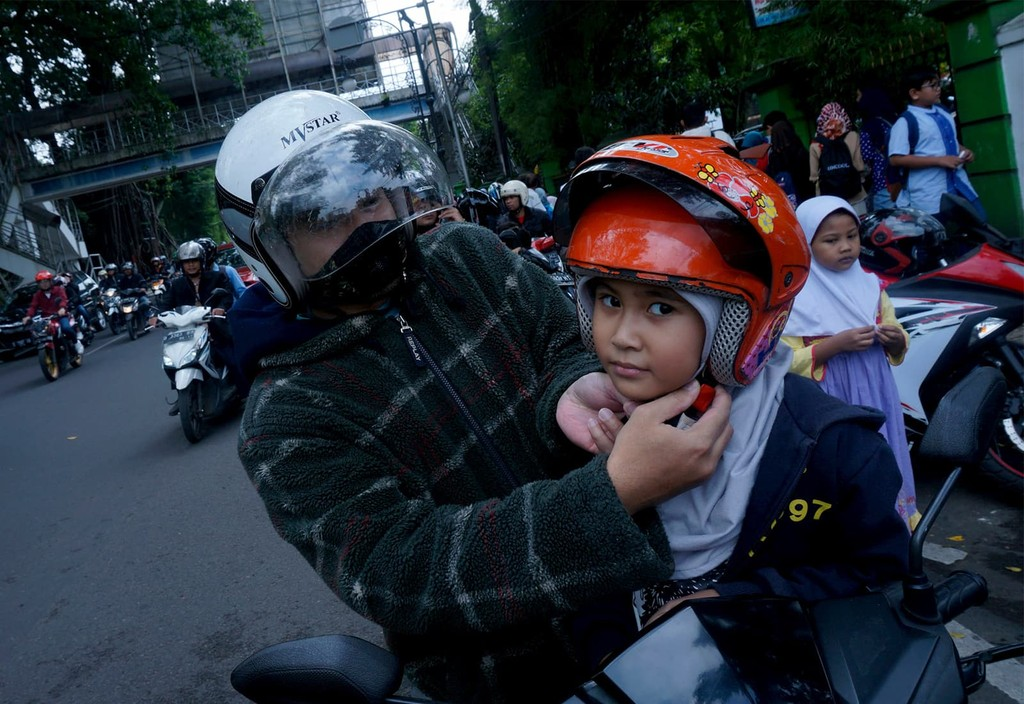 Bicyclists in Bandung, Indonesia wearing helmets as part of Bloomberg Philanthropies Road Safety program.