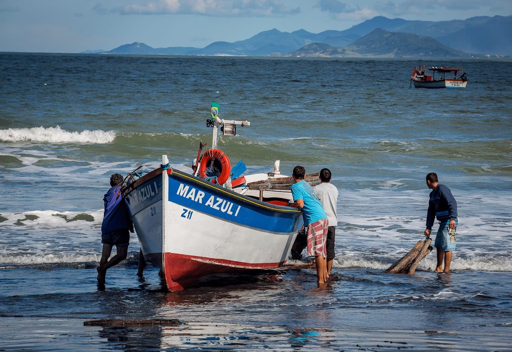 Fishermen in Fortaleza, Brazil stand on the shore by their boat. Photo credit: Bento Viana Photography