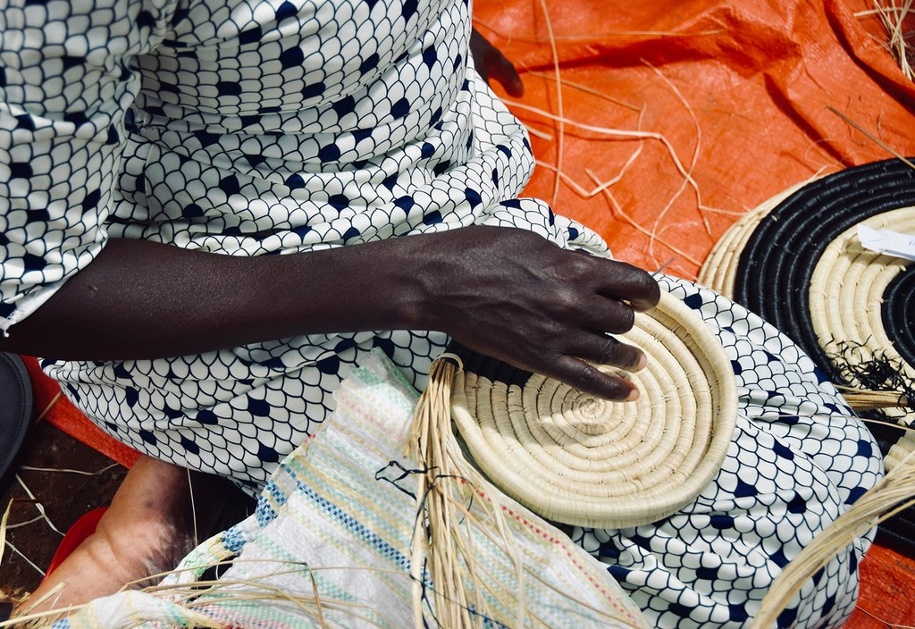 The beginning stages of a utensil holder on the lap of an artisan weaver in Uganda. Photo credit: Nest