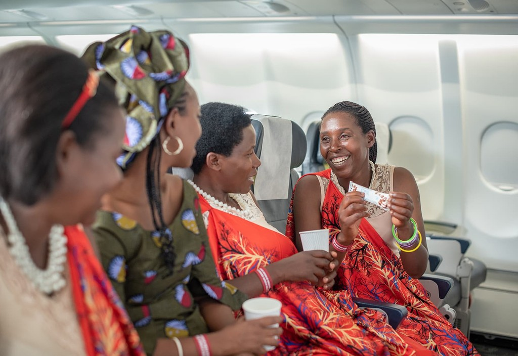 Women enrolled in Bloomberg Philanthropies' training programs with Sustainable Growers enjoy their very own specialty coffee aboard a RwandAir flight. Since 2018, Question Coffee is served across all RwandAir flights throughout Africa, Europe, the Middle East, and Asia.